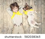 smiling boy with dog on a floor | Shutterstock . vector #582038365