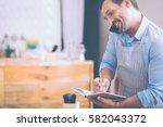 pleasant man talking on phone | Shutterstock . vector #582043372