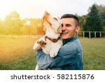 Stock photo happy young man holding dog labrador in hands at sunset outdoors 582115876