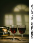 Small photo of Two antique glasses filled with claret. Vintage telephone in the background