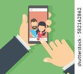 men on the screen. hand holding ... | Shutterstock . vector #582162862