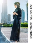 Small photo of Arabian businessman reading a message. Arab businesswoman hijab holding cell phone on the street on a background of skyscrapers of Dubai. The woman is dressed in a black abaya