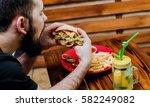 young man eating a cheeseburger.... | Shutterstock . vector #582249082