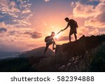 People helping each other hike up a mountain at sunrise.  Giving a helping hand, and active fit lifestyle concept. - stock photo