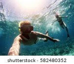 Small photo of Making selfie underwater with action camera. Couple snorkeling in deep blue sea.