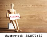 Small photo of Mannequin holding paper with word BACKCARE on wooden background