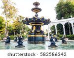 Water gold fountain. Outdoor fountains from gold in local park. Golden Garden fountains in ornamental design in park with small statues.Small bronze statues angels fountains in park - stock photo