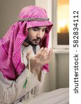 Small photo of Portrait of devout man is wearing Islamic clothes while praying to the Allah at home