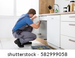 Stock photo repairman in overalls repairing cabinet hinge in kitchen 582999058