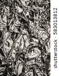 Small photo of Crumpled wrinkled silver foil texture closeup metallic material