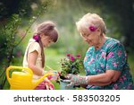 Stock photo happy grandmother with her granddaughter working in the garden 583503205