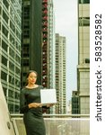 Small photo of African American Businesswoman working in New York, wearing black long sleeve crop top, skit, stands by railing on balcony facing street with buildings, works on laptop computer. Color filtered effect