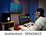 asian male DJ working in digital broadcasting studio, online radio station, podcast, post production technology - stock photo