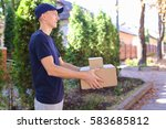 Small photo of Deliveryman Carring Parcel and Giving it and Smiling. International Staffing Company Shows That Courier of Company Always Ready to Work at Any Time and Any Day, Young Man of European Appearance in