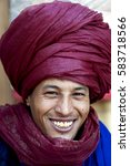 Small photo of Bedouin nomad, Ait Benhaddou, Morocco, 2016. Portrait of a Bedouin nomad with scarlet turban and big smile selling his wares in popular tourist spot and world heritage site of Ait Benhaddou, Morocco.