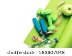 Small photo of Fitness concept - yoga mat, apple, dumbbells and skipping rope on the white background