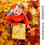 Little girl in autumn orange leaves and gift box. Outdoor. - stock photo