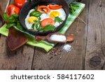 breakfast with fried eggs on pan | Shutterstock . vector #584117602