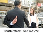Two business people shaking hand making a deal but Business man holding crossed fingers behind back while Business woman smiling, Betray concept.