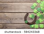 Stock photo background with rusty horseshoe and paper clover leaves on the old wooden boards st patrick s day 584243368