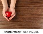 female hands holding red heart...   Shutterstock . vector #584442256
