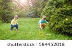 kids on easter egg hunt in... | Shutterstock . vector #584452018