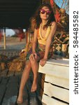 Small photo of Young sunburned girl in the bright boho dress and mirror sunglasses seating on the bar tend barefoot.
