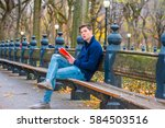 Small photo of Young man wearing blue sweatshirt, fashionable destroyed jeans, gray casual shoes, sits on long bench at Central Park, New York in autumn day, crossing legs, reads red book.