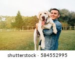 Stock photo portrait of happy man holding his friend dog labrador at sunset in park 584552995