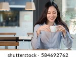woman drinking coffee at a...   Shutterstock . vector #584692762