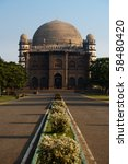 A walkway leads to the Golgumbaz, a Mughal mausoleum in Bijapur, India. - stock photo