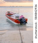 Small photo of A panga boat is seen along the beach in Isla Mujeres, Mexico during sunset
