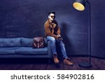 handsome young man sitting on... | Shutterstock . vector #584902816