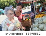 Young Woman Helping Elderly...