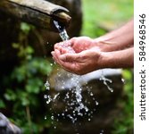 Small photo of man washing hands in fresh, cold, potable water of mountain spring