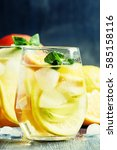 Small photo of White sangria with fruit and ice, gray-silver background, selective focus