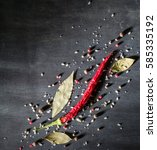 Small photo of Red pepper pungent spices and bay leaf on the black tree. View from above. Space for text.
