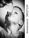 Quench thirst. The boy is drinking mineral water from plastic bottle. BW portrait with strong  vignetting. - stock photo