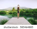 young woman stands on a wooden... | Shutterstock . vector #585464885