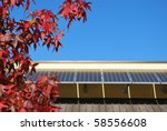 Solar panels on the roof against blue sky in autumn, focus on the tree, free copy space - stock photo