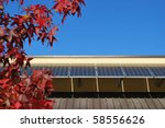 Solar panels on the roof against blue sky in autumn, focus on the panels, free copy space - stock photo