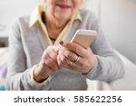 senior woman holding smartphone | Shutterstock . vector #585622256
