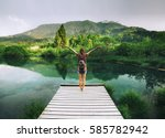 young woman stands on a wooden... | Shutterstock . vector #585782942