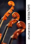 Small photo of Violin heads close up between two blurry fiddle head