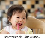 baby eating messy mashed potato | Shutterstock . vector #585988562
