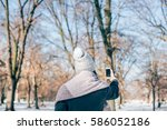 woman taking a photo of snowy... | Shutterstock . vector #586052186