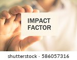 Small photo of Closeup on businessman holding a card with text IMPACT FACTOR, business concept image with soft focus background and vintage tone