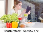woman checks the recipe on her... | Shutterstock . vector #586059572