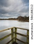 Small photo of Long exposure image of Arrow Valley ake in Redditch, worcestershire with moving clouds and still water