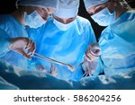 Small photo of Group of surgeons at work in operating theater toned in blue. Medical team performing operation